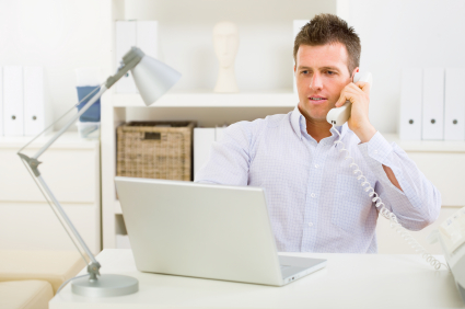 Businessman working on laptop, talking on phone