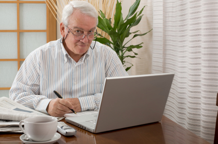 Senior man working from home with a laptop