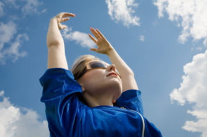 The girl in sunglasses reaches for the sky