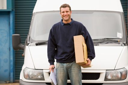 Delivery person standing with van holding clipboard and box